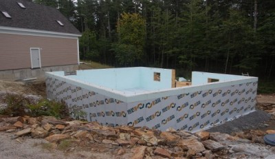 The waterproofing membrane is applied right down to the exterior perimeter drain that is covered in crushed stone.