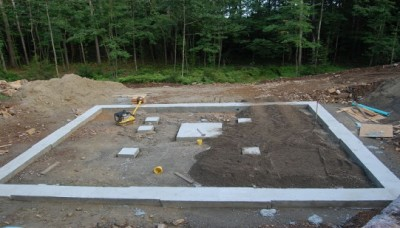 After the forms for the footers are removed gravel is brought in and compacted. Interior perimeter drains are installed.